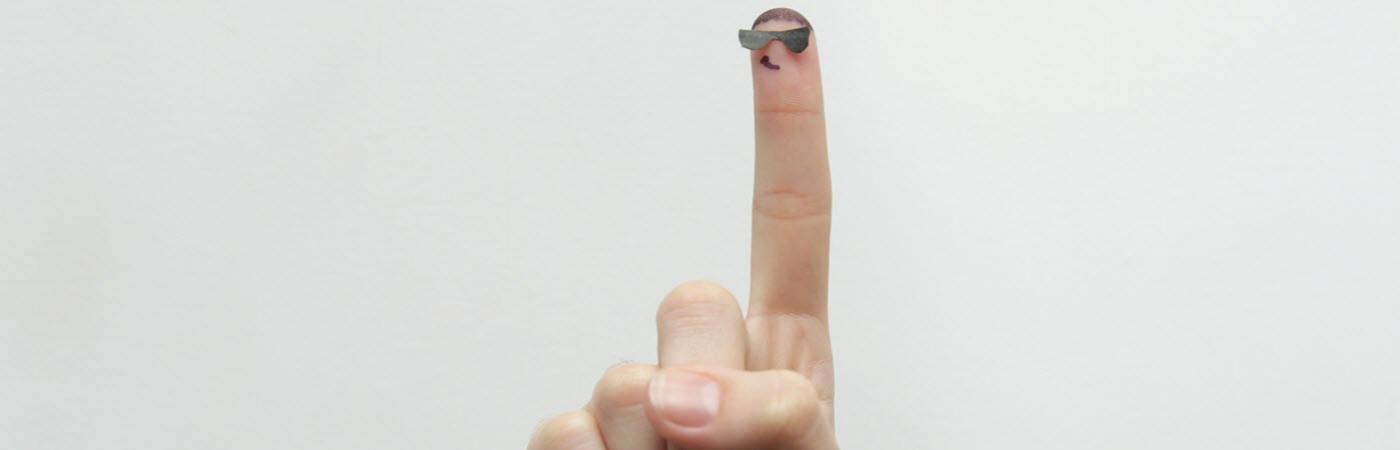 Zeigefinger mit Gesicht: Die Fingerspitze ist eine klassische Stelle zur Blutabnahme zum Blutzucker messen.