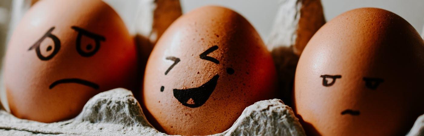 Eier mit aufgemalten Gesichtern und unterschiedlichen Launen: Stimmungsschwankungen bei Diabetes.
