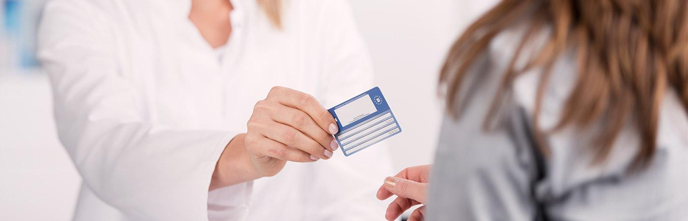 Ärtin übergibt Patientin die Versicherungskarte