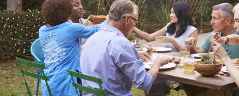 Leute sitzen am Tisch zusammen und essen