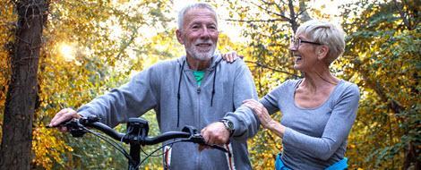 Älteres Paar mit Fahrrad im Wald: Im Alter gelten für den Blutzucker andere Normwerte.