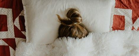 Frau vergräbt sich mit Erkältung unter Decke.