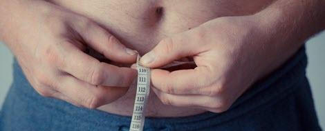 Mann mit starkem Übergewicht misst seinen Bauchumfang mit einem Maßband.