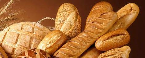 Verschiedene Brotsorten liegen auf einem Holztisch.